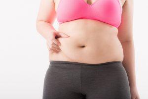 お腹の脂肪をつかむ女性