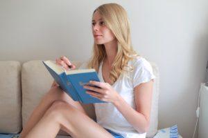 ソファで日記を書く女性