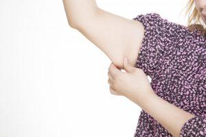 二の腕の脂肪をつかむ女性