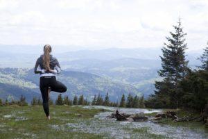 山の上で片足立ちする女性