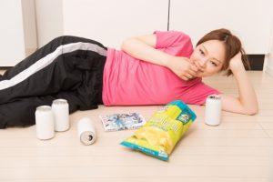 横になってお菓子を食べる女性