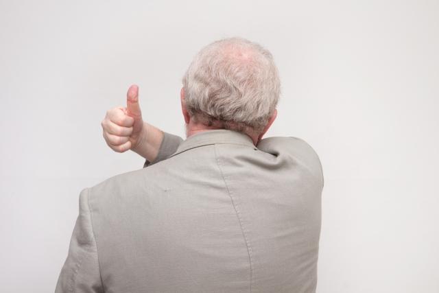 親指を立てる後姿の男性