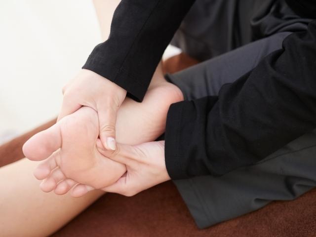 足裏のセルフマッサージをする女性