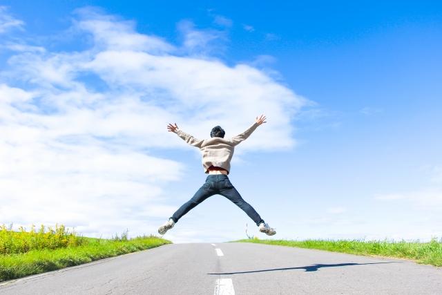 青空の下で飛び跳ねる男性