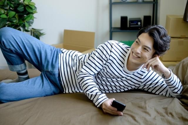 横になってテレビを見る男性