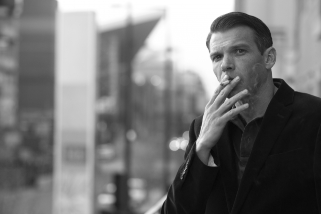 たばこを吸いながらたそがれる男性