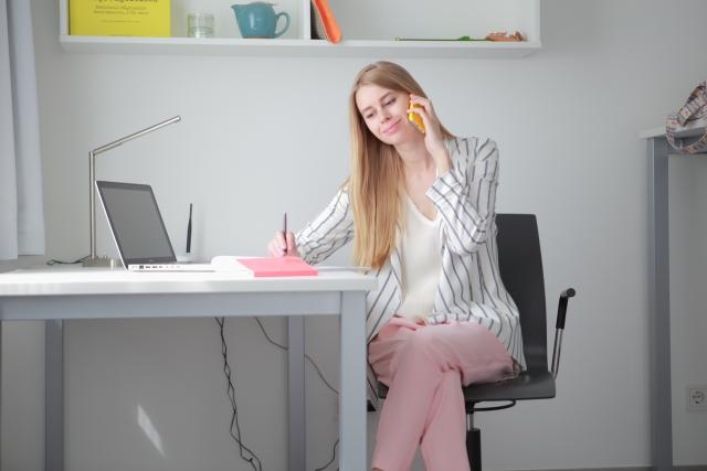 デスクで仕事中に足を組む女性