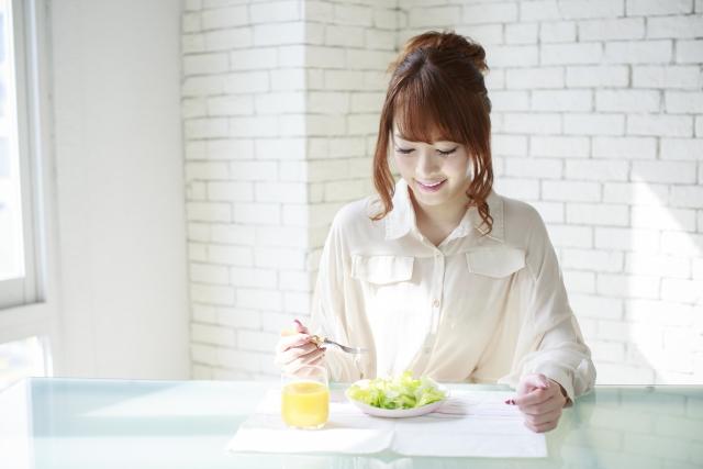 笑顔で朝食をとる女性