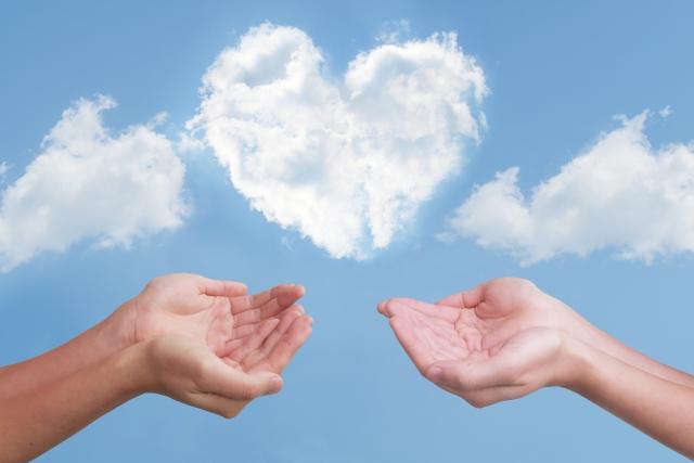 ハート型の雲と2人の手