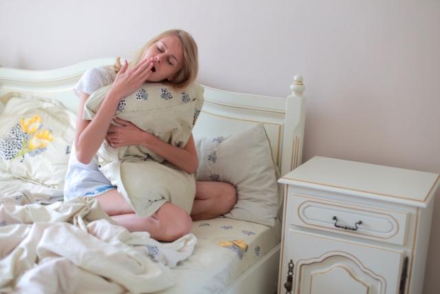 ベッドの上の眠そうな女性