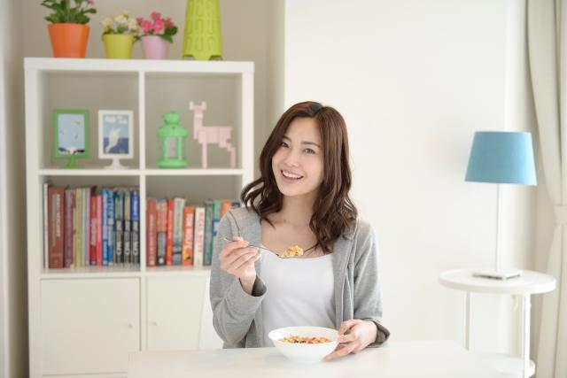 笑顔で朝食を食べる女性