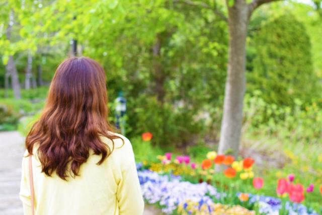 散歩する女性とキレイな花