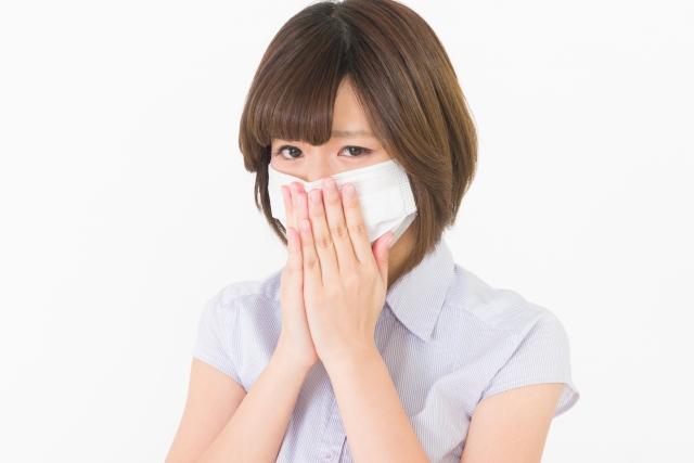 マスクをつけて臭いを防ぐ女性