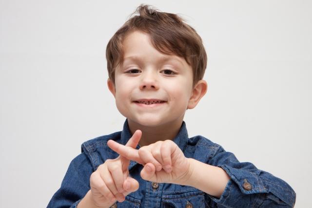 バツ印を作る子供