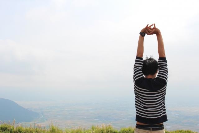山頂で伸びをする男性