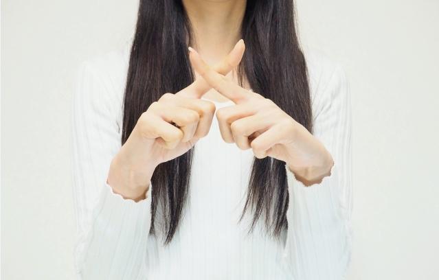 バツ印を作る女性