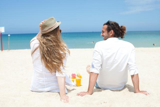 砂浜で談笑するカップル