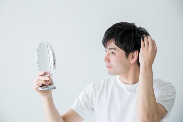 鏡で髪の毛をチェックする男性