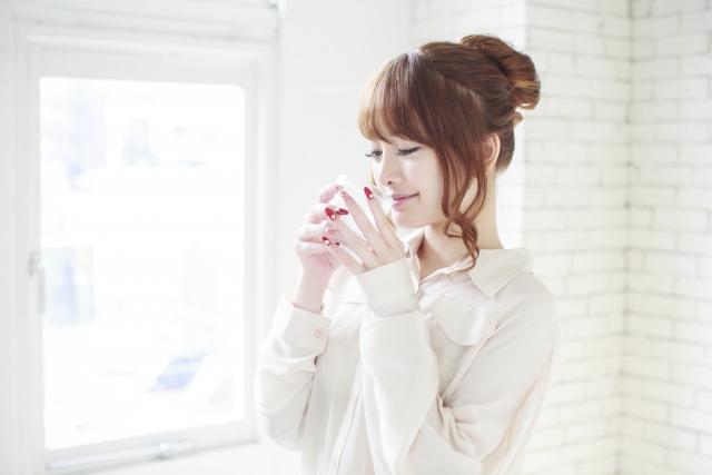 笑顔で飲み物を口にする女性