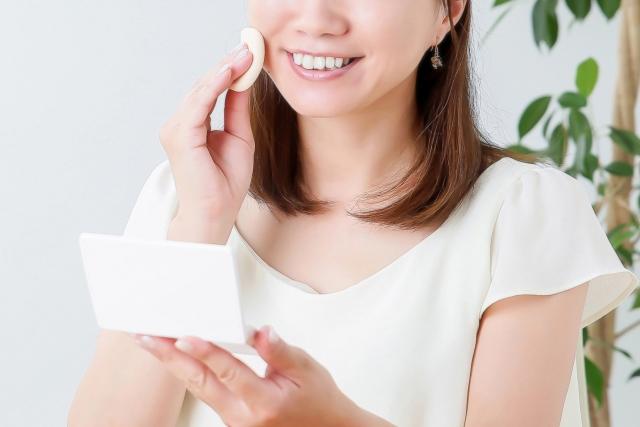 笑顔で化粧をする女性