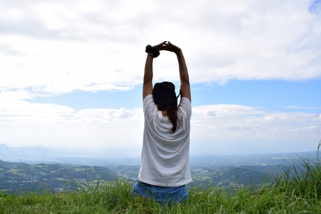 景色の良い場所で伸びをする女性