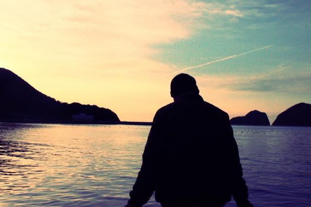 海辺でたたずむ男性