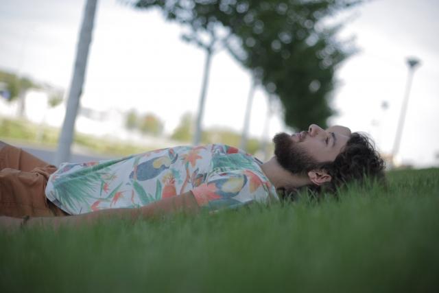 芝に寝そべって考え事をする男性