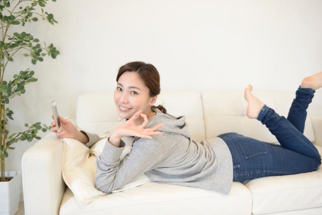 ソファでスマホを使う女性
