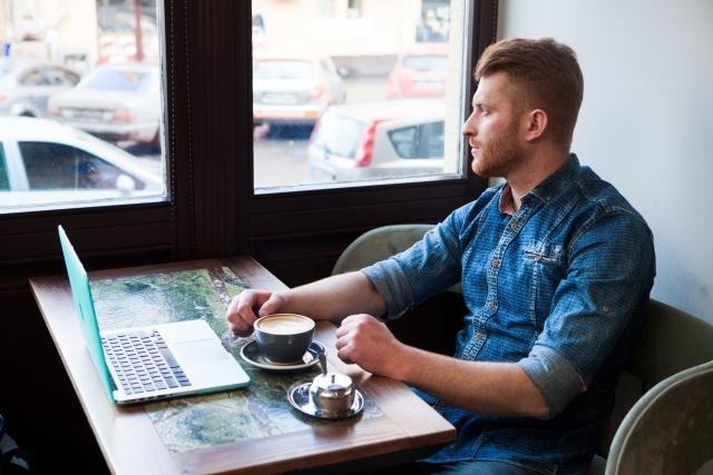 窓の外を見ながら考え事をする男性