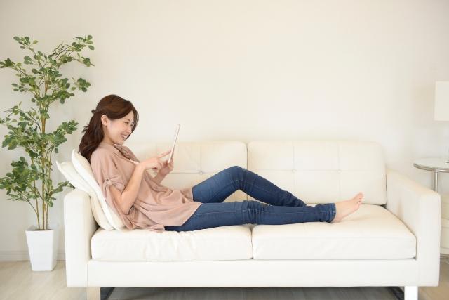 ソファでリラックスして動画を見る女性